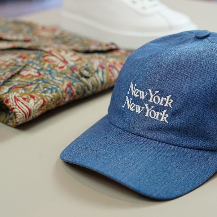 A photo of a blue New York cap and Corridor paisley printed jacket. on a white table.
