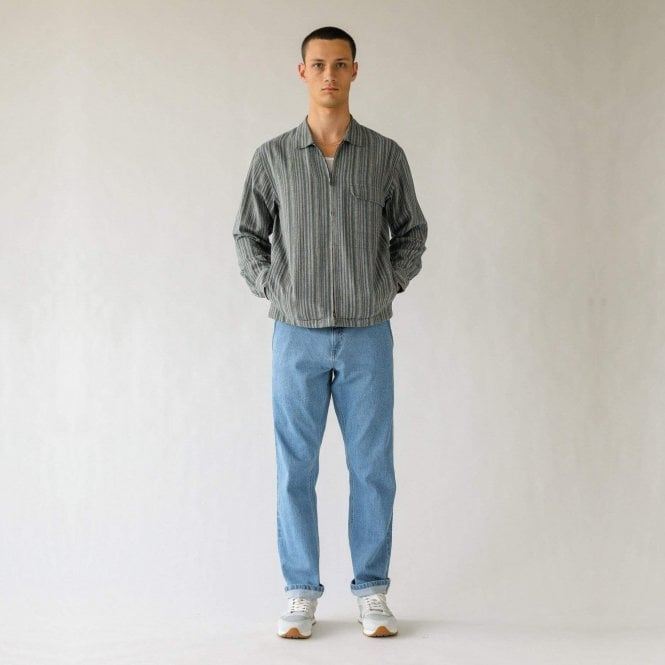 A photo of a man modelling a Corridor blue striped zip jacket and blue jeans.